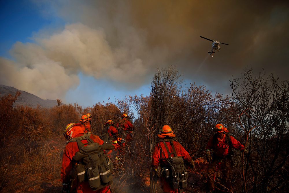 A helicopter flies overhead as inmate firefighters battle the Wildomar wildfire in the Cleveland National Forest on Thursday, October 26, 2017 in Wildomar, Calif. The fire started after a motorcycle crashed into a tree. © 2017 Patrick T Fallon