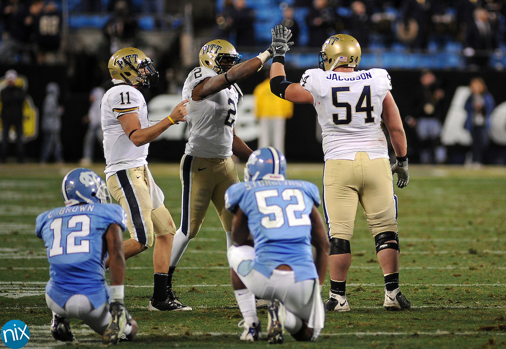 Pittsburgh's Bill Stull (11) Dorin Dickerson (2) and Chris Jacobson celebrate after North Carolina committed an offsides penalty on a fourth to give the Panthers a first down during the Meineke Car Care Bowl Saturday night at Bank of America Stadium in Charlotte. Pittsburgh won the game 19-17.