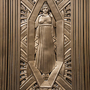 The Art Deco decorations are bronze metal work on door of  building on 34th Street and 8th Avenue in NYC.