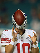 New York Giants quarterback Eli Manning (10) grabs a football directly in front of his face as he warms up before the NFL week 14 regular season football game against the Miami Dolphins on Monday, Dec. 14, 2015 in Miami Gardens, Fla. The Giants won the game 31-24. (©Paul Anthony Spinelli)