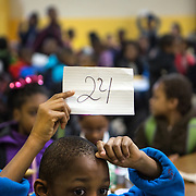 WASHINGTON, DC - APR 24: Excited students hold up their raffle numbers hoping they have the winning number during the daily morning raffle in the cafeteria at Simon Elementary School in Washington, DC, April 24, 2014. DC has enormous truancy rates, even among young children. In the last year or two, the school system has made a big push to improve attendance. Simon Elementary is seen as a model, introducing incentives and games that are tied to attendance and meant to get kids excited about coming to school; systems to ensure that parents get a call home whenever their kids are absent; weekly attendance meetings to talk about kids who are missing too much school; and a partnership with a community based organization that can make home visits and connect families with services. (Photo by Evelyn Hockstein/For The Washington Post)