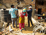 01 MARCH 2017 - KHOKANA, NEPAL: Men fill a laborer's basket with sand that she would carry to a nearby construction site to rebuild a home destroyed in the 2015 earthquake. Recovery seems to have barely begun nearly two years after the earthquake of 25 April 2015 that devastated Nepal. In some villages in the Kathmandu valley workers are working by hand to remove ruble and dig out destroyed buildings. About 9,000 people were killed and another 22,000 injured by the earthquake. The epicenter of the earthquake was east of the Gorka district.     PHOTO BY JACK KURTZ