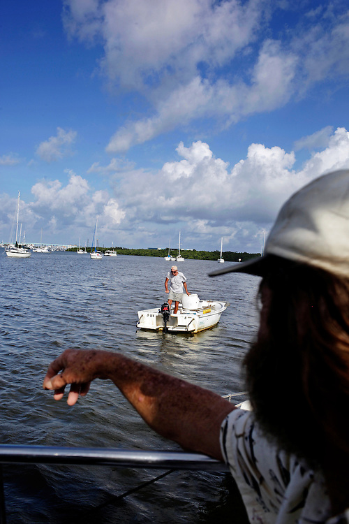A man by the nickname of Hillbilly Jim, center, who lives on a boat anchored in Estero Bay, Fla. heads back to his home after talking with Randy Eibler, right, who has lived on a boat for 34 years. Eibler said for the most part, people who live on their boats tend to anchor near each other to form a community and watch out for one another.