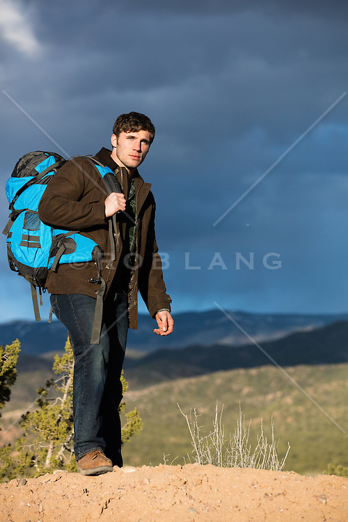 good looking man hiking on a mountain range at sunset