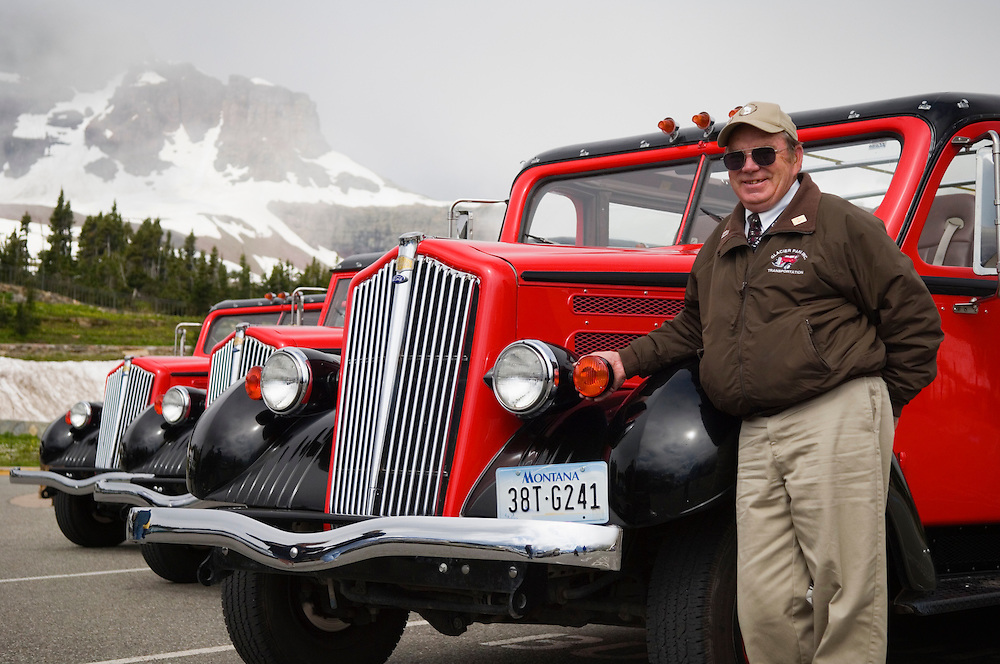 "Driver/Guide Robert Ferguson with his ""Jammer"" tour bus at Logan Pass, Glacier National Park, Montana."