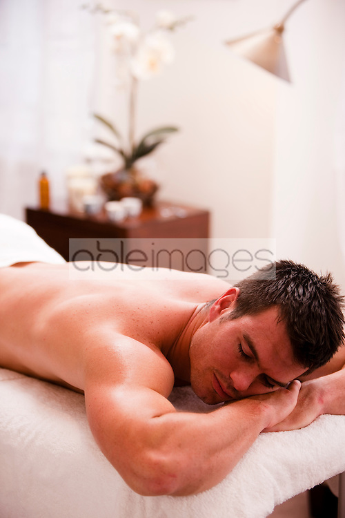 Close up of a man lying on his stomach on a treatment bench