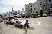 Een man loopt een steile heuvel in San Francisco omhoog. De Amerikaanse stad San Francisco aan de westkust is een van de grootste steden in Amerika en kenmerkt zich door de steile heuvels in de stad.<br /> <br /> A man walks at a steep hill in San Francisco. The US city of San Francisco on the west coast is one of the largest cities in America and is characterized by the steep hills in the city.