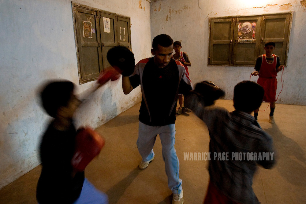KARACHI, PAKISTAN - OCTOBER 12: An elder members of the Young Baloch Boxing Club helps his younger brothers train, Sunday, October 12, 2008, in Karachi, Pakistan. Lyari is Karachi's poorest, most dangerous, drug and crime-infested slum, but has produced the bulk of Pakistan's champion boxers. Boxing has been a way of survival for many of the young men, who are often sponsored by corporations and event the military, to box for them at events throughout the city and the country. Lacking in the most basic resources, including a sufficient diet, the young boxers have watched countless champions on television throughout the years, attempting to emulate their abilities. (Photo by Warrick Page)