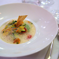 Slow-cooked skate wing served on a broth of spiced coconut milk and Kafir lime, tomato confit and sauteed spring vegetables at the Relais & Chateaux La Cote Saint-Jacques,