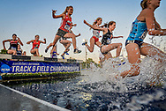 Athletes hurdle an obstacle during steeplechase at the NCAA Division 1 East Region Track and Field meet at the University of Kentucky in Lexington, Kentucky, May 25, 2017.