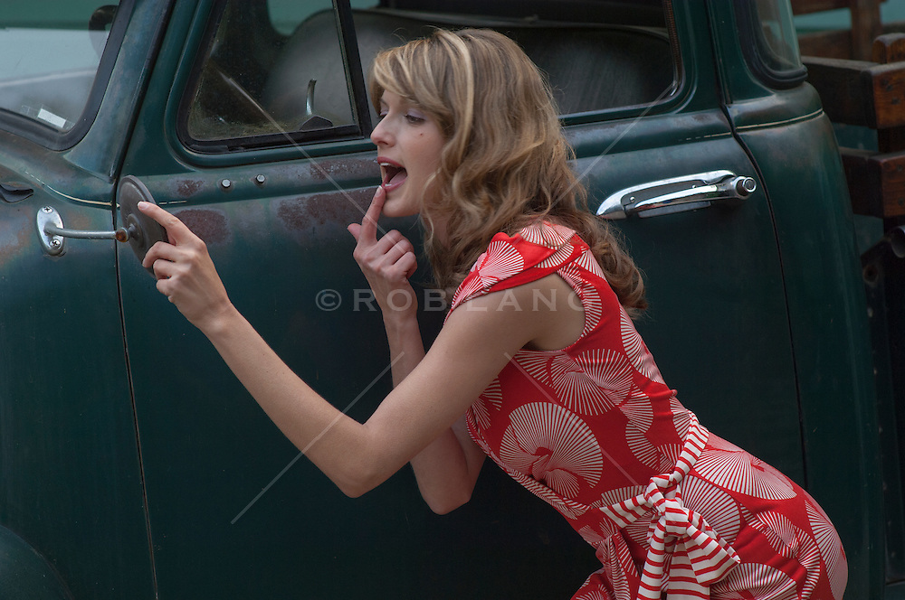 beautiful woman putting lip gloss on while using a rear view mirror on an old truck