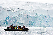 "Zodiac with exploration eco-tourists in front of the mighty glacier in ""Fjortende Julibukta"" (79 degrees N), Spitsbergen, Svalbard"