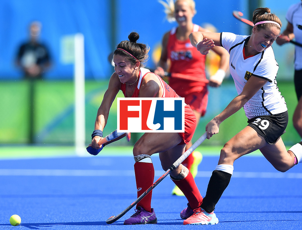 Germany's Pia-Sophie Oldhafer (R) geatures after being hit with a stick by The USA's Melissa Gonzalez (L) during the women's quarterfinal field hockey USA vs Germany match of the Rio 2016 Olympics Games at the Olympic Hockey Centre in Rio de Janeiro on August 15, 2016. / AFP / MANAN VATSYAYANA        (Photo credit should read MANAN VATSYAYANA/AFP/Getty Images)