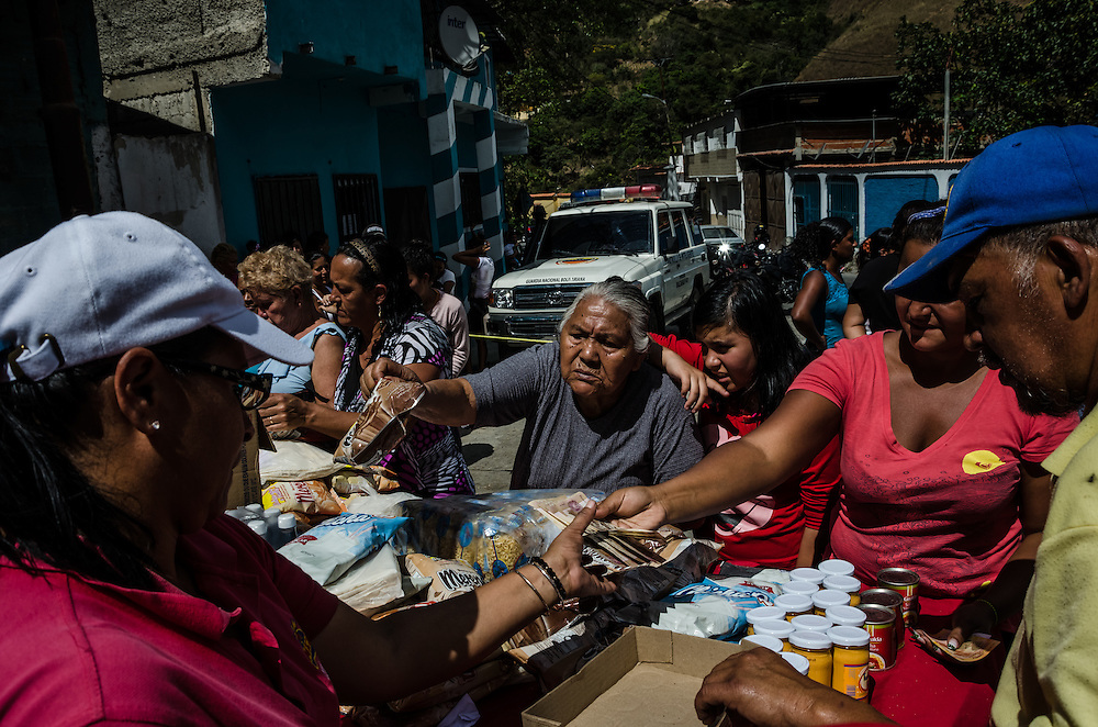 """LOS TEQUES, VENEZUELA - JANUARY 18, 2015: Hundreds of people lined up to purchase difficult to find food items, such as sugar, cooking oil, and rice, at subsidized prices during a government """"Mercal"""" event in Los Teques. Despite being a petro-state with one of the largest oil reserves in the world, basic food goods are difficult to find in stores across Venezuela."""