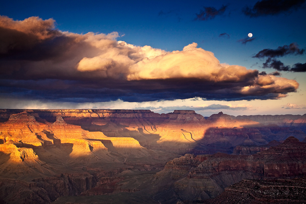 The moon rising as the setting sun bathes the Grand Canyon in a warm light. From Hopi Point on the South Rim.