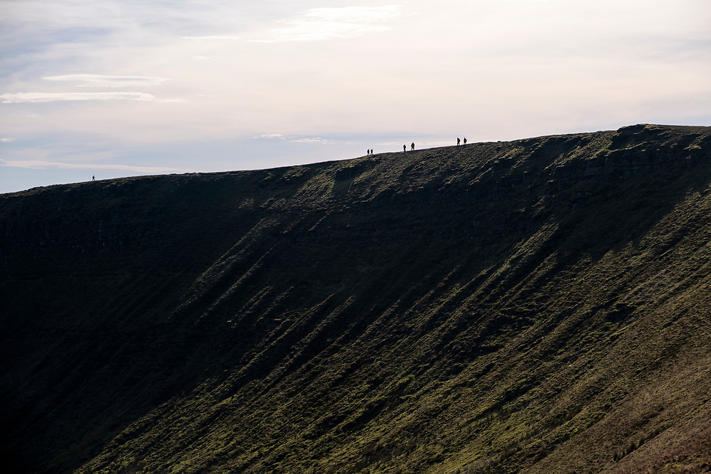 Silhouette of people walking across the mountain ridge between the twined peaks of Pen Y Fan and Corn Du in Brecon Beacons National Park, Wales, Powys, United Kingdom.  Pen Y Fan is the highest point in the Brecon Beacons hill and mountain range in South Wales. The National Park was established in 1957 due to the spectacular landscape which is rich in natural beauty and is run by the National Trust.  (photo by Andrew Aitchison / In pictures via Getty Images)