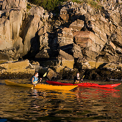 A man and woman sea kayaking near Burnt Porcupine Island in Maine's Acadia National Park.  Bar Harbor.
