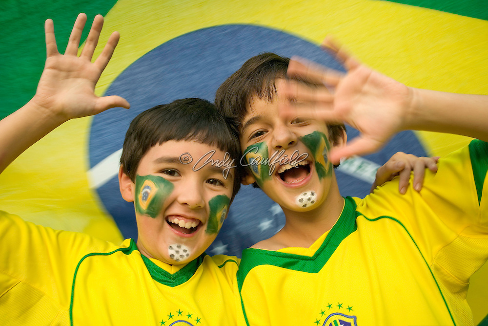 Boys (9 yrs old) celebrating with Brazilian Flag face paint wearing team colors of Brazilian National Soccer team against Brazilian Flag background.<br /> BRAZIL                     MODEL RELEASED