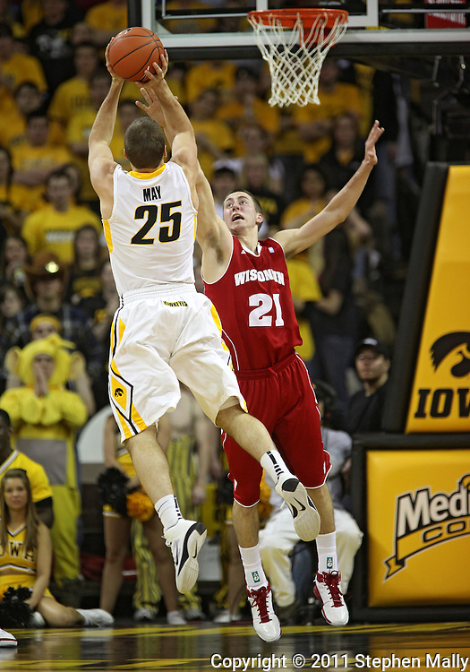 February 09 2011: Wisconsin Badgers guard Josh Gasser (21) tries to block a shot by Iowa Hawkeyes guard/forward Eric May (25) during the first half of an NCAA college basketball game at Carver-Hawkeye Arena in Iowa City, Iowa on February 9, 2011. Wisconsin defeated Iowa 62-59.