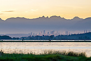 Boundary Bay, Burnaby's Metrotown and the North Shore (Pacific Coast Range) Mountains.  Photographed from Blackie Spit in Surrey, British Columbia, Canada