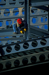 Stock photo of a construction worker perched on a beam at the construction site