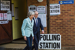 Sonning, UK. 23 May, 2019. Prime Minister Theresa May leaves her local polling station with her husband Philip after voting in the European elections.