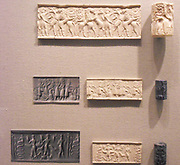Cylinder seals with impressions, from Mesopotamia. Top: seal made from marble depicting a hero in battle with animals. Early Dynastic Period, 2500-2350 BC; Centre: seal made from Lapis Lazuli depicting a battle between gods. Early Akkadian Period, 2350-2250 BC; Bottom: seal made from metadiorite, depicting a snake god and other deities with snake, scorpion and goat features. Akkadian Period, 2350-2150 BC.