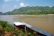 A boats await their daily travels with tourists, Mekong River, Luang Prabang, Laos.