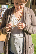 Young woman trying on jewlery at the Thousand Springs Art Festival at Ritter Island near Hagerman, Idaho. MR
