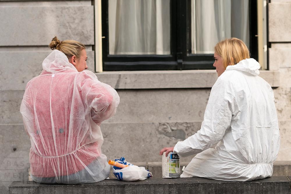 In Utrecht zitten twee meisjes in beschermende kleding en verfspullen op een muur voor het stadhuis.<br /> <br /> In Utrecht two girls in protective clothes and painting materials sit in front of the town hall on a wall.