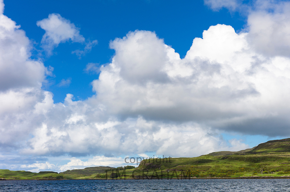 Puffy white Cumulus cloud formation above Dunvegan Loch, Isle of Skye, Western Scotland