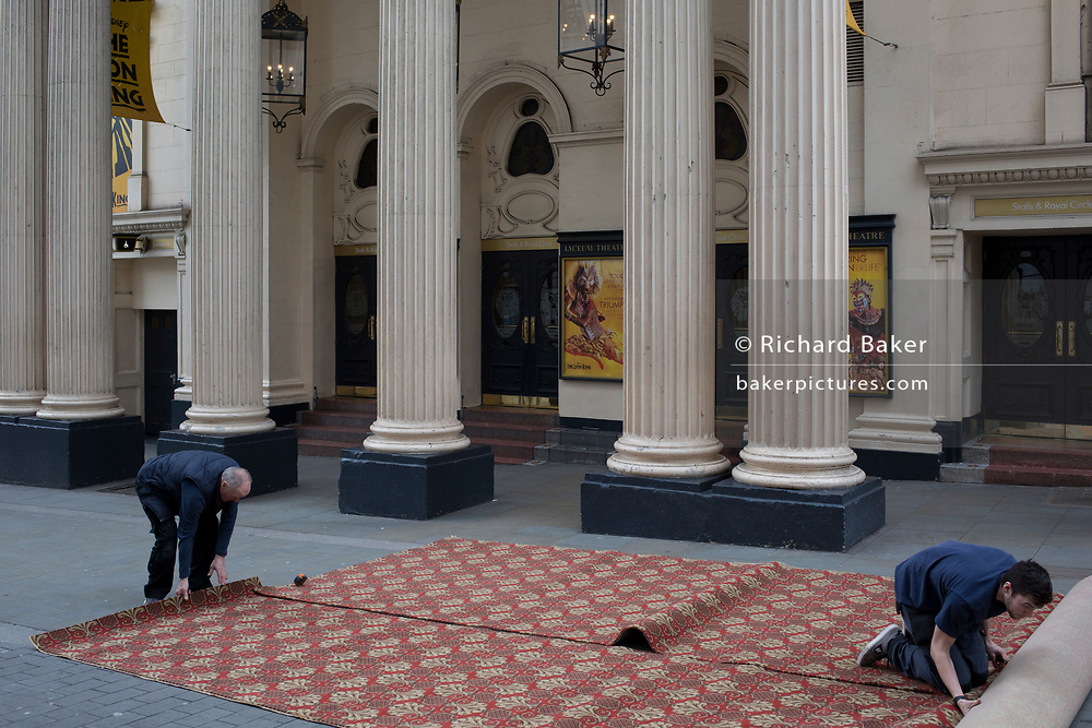 Carpet fitters trim a new carpet in the street for the interior of the Lyceum Theatre on Wellington Street, on 5th March 2019, in London, England.