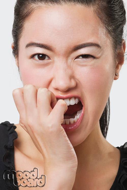 Close-up of frustrated Chinese woman over white background