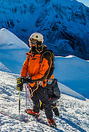 A climber rests on the main ice wall leading to the summit of Island Peak.