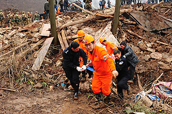 Rescuers remove a body from the mud-inundated debris after a landslide hit Gaopo Village in Zhenxiong County, southwest China's Yunnan Province, Jan. 11, 2013. Twenty-six have been confirmed dead after the landslide hit the mountainous region on Friday morning. About 40 are believed to have been buried in the landslide, according to an initial investigation. Rescuers continue their efforts to search for the missing people, January 11, 2013. Photo by Imago / i-Images...UK ONLY