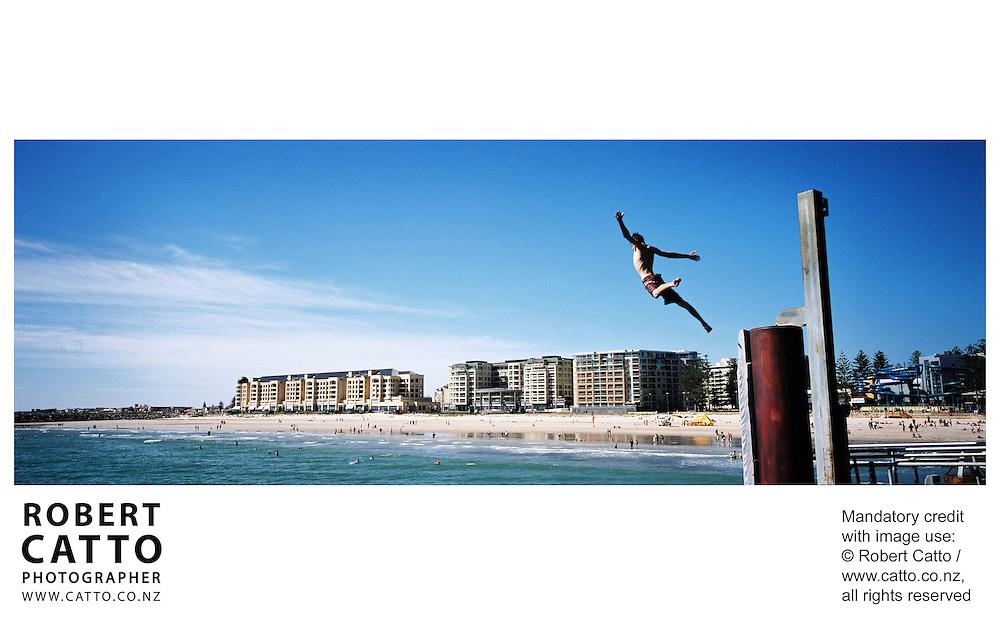 Kids jump from the pier at Glenelg, Adelaide, South Australia (SA), Australia.