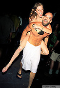 SPECIAL PRICE. APPROVAL REQUIRED.<br /> <br /> Mike Manumission carrying his wife Claire naked on his back, Manumission at Priviledge, Ibiza 1999