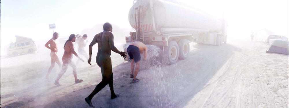 """Nude citezens of Black Rock City try to stay cool as the chase a water truck through the desert during the16th annual Burning Man festival September 1, 2001 in the Black Rock Desert near Gerlach, Nevada.An estimated record 29,000 people camped out on a remote desert playa, or dry lake, for the week-long counter-cultural celebration of art and """"radical self-expression."""" This year's theme was thethe stages of man."""