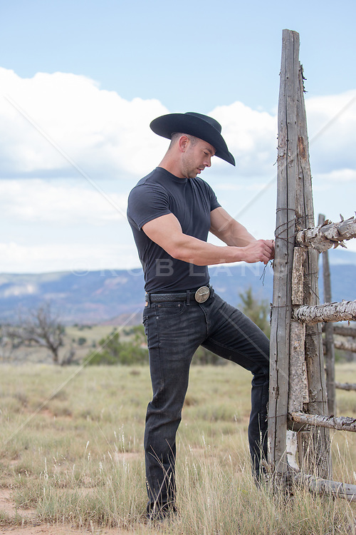 hot cowboy working on a rustic fence