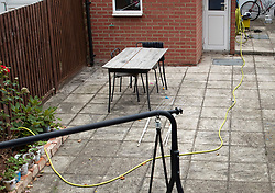 NOTE TO EDITORS : IMAGE TAKEN FROM A SUPERMARKET CAR PARK © Licensed to London News Pictures. 19/07/2019. London, UK. A garden hose lies across a patio in the back garden of a house where it is reported that the body of a woman was found on fire in Chadwell Heath, East London. Fire fighters arrived at the house and then called in the police when they found the woman. Photo credit: Peter Macdiarmid/LNP
