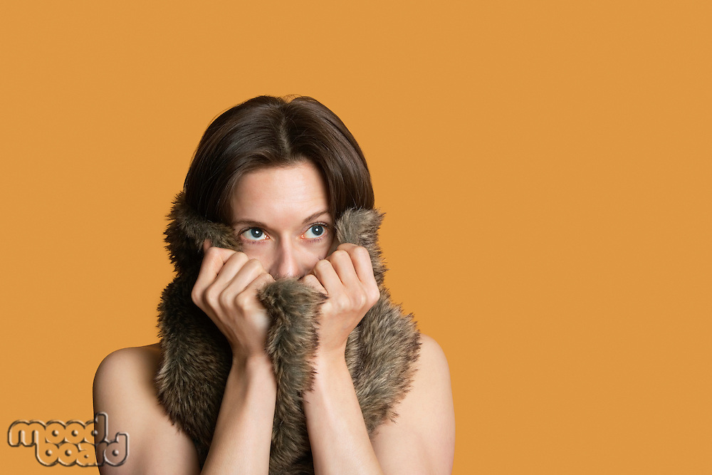 Close-up of woman with fur on face looking away over colored background