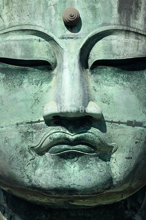 extreme close up of the face of the Great Buddha of Kamakura Japan