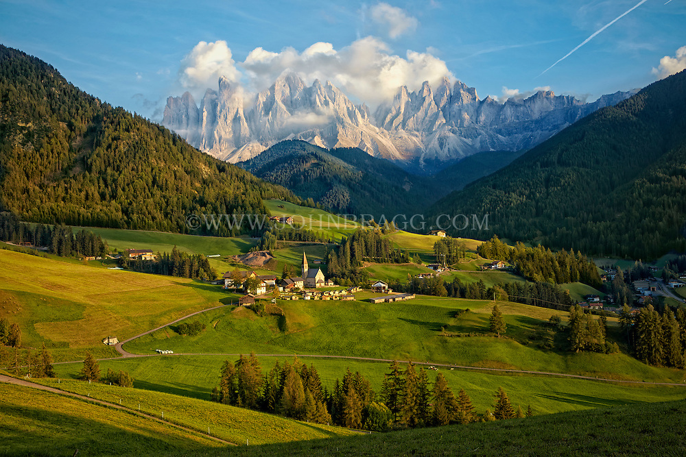 A distant view of St. Magdalena Village with Dolomites mountain range in distance.