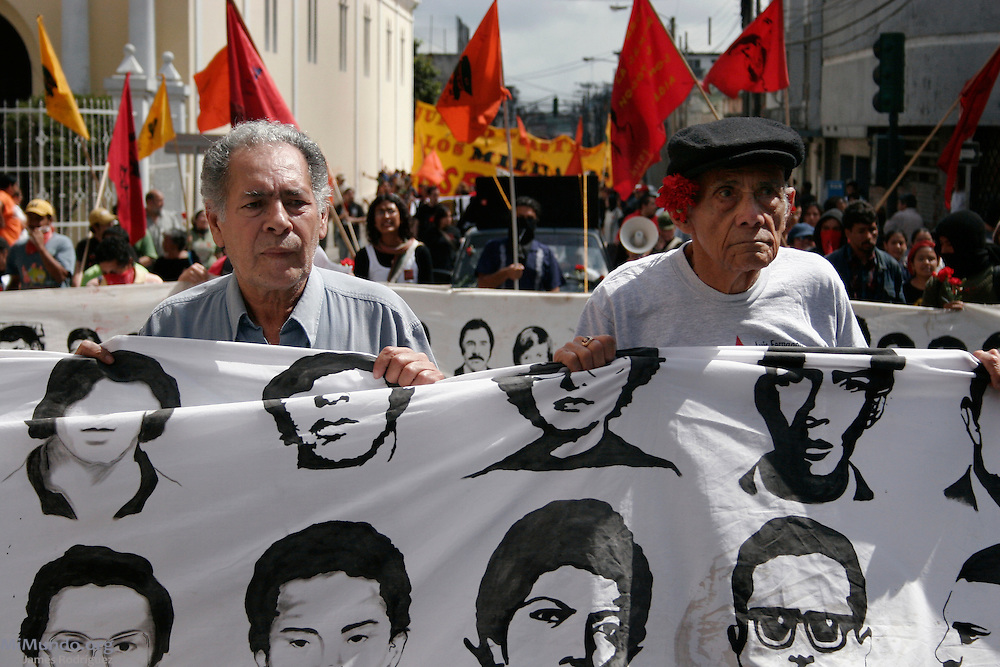 "Human rights activists and public figures Miguel Angel Albizures (left) and Alfonso ""Poncho"" Bauer Paiz hold a banner with the faces of a handful of Guatemala's 45,000 forcibly disappeared victims as the March for Remembrance continues through Guatemala City's historic center. Organized by H.I.J.O.S. (Sons and Daughters for Identity and Justice Against Forgetfulness and Silence), the March for Remembrance is a counter march to the annual Military Day parade, seen by many as inadequate in modern Guatemala considering the atrocities carried out by the institution against the local population during the 36-year internal armed conflict. Guatemala City, Guatemala. June 30, 2007."