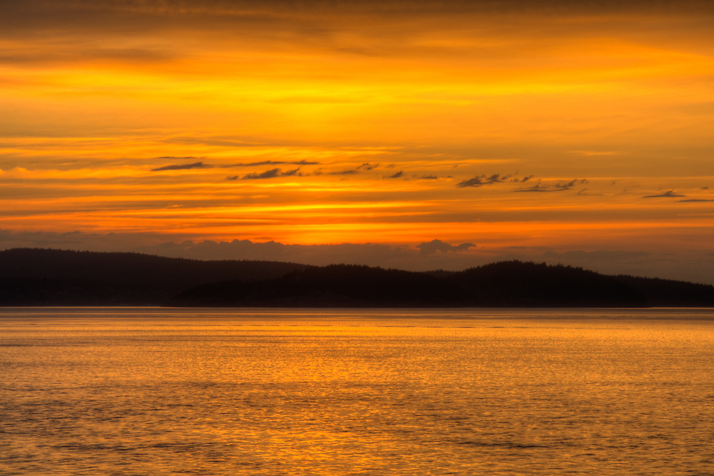 An insanely vibrant and colorful sky Rosario Strait as the sun sets behind Washington's  Decateur and Lopez Islands in the Strait of Juan de Fuca. About 35 miles due west in this direction is Victoria, British Columbia, Canada.