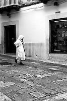 Una suora passeggia per le vie di Ostuni e la sua attenzione viene catturata da una vetrina che espone oggetti di artigianato locale