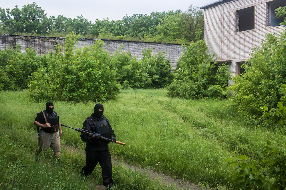 DNIPROPETROVSK REGION, UKRAINE - MAY 19: Militiamen walk back to their barracks at a training camp for the Donbass Battalion, a pro-Ukrainian militia, on May 19, 2014 in Dnipropetrovsk Region, Ukraine. A week before presidential elections are scheduled, questions remain whether the eastern regions of Donetsk and Luhansk are stable enough to administer the vote. (Photo by Brendan Hoffman/Getty Images) *** Local Caption ***