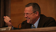 Senator  Jon Tester D-MT jokes with Herbert M. Allison Jr.  as Allison testifies before the Senate Banking, Housing and Urban Affairs Committee during his confirmation hearing for the position of Assistant Secretary of the Treasury for financial stability on June 4, 2009.  Photograph by Dennis Brack