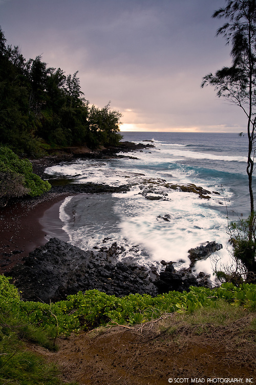 View of crashing waves from small red sand beach in Hana, Maui, Hawaii