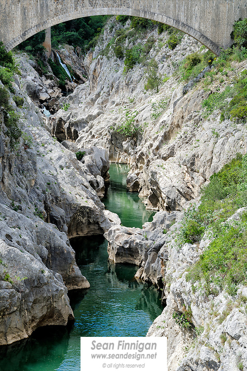 An arch of the Devil's bridge, le Pont du Diable, a masterpiece of Romanesque art, built in 1031 by Benedictine monks, spanning the gorge of the Hérault River. The bridge linked Saint-Jean-de-Fos and Saint-Guilhem-le-Desert and facilitated the crossing of the Hérault by pilgrims en route to Saint Jacques de Compostela. The bridge overlooks the deep green waters of the Hérault, which in places reach a depth of between 200 and 300 metres in places, and are home to a wealth of uniquely Mediterranean flora and fauna. A paradise for hiking, kayaking and close to a nearby river beach one of the finest bathing spots of the area.